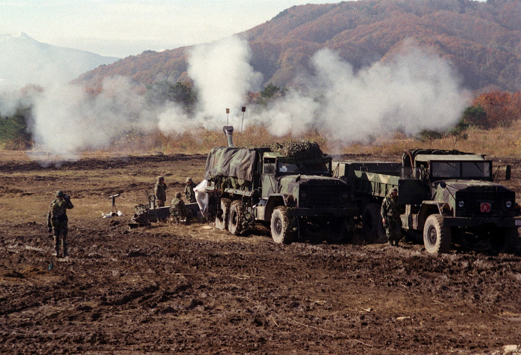 Right side front view long shot of two M923A1 (6X6) 5-ton cargo trucks as they obscure the view of a M198 155mm Howitzer that's being fired by US Marines from Lima Battery, 3rd Battalion, 12th Marines, out of Camp Hansen, Okinawa, Japan. The training is taking place at the Artillery Relocation Shoot at Ojojihara, Japan