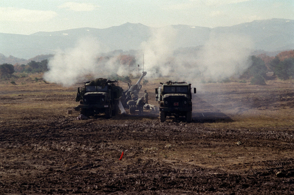 Straight on long shot of two M923A1 (6X6) 5-ton cargo trucks as they obscure the view of a M198 155mm Howitzer that's being fired by US Marines from Lima Battery, 3rd Battalion, 12th Marines, out of Camp Hansen, Okinawa, Japan. The training is taking place at the Artillery Relocation Shoot at Ojojihara, Japan