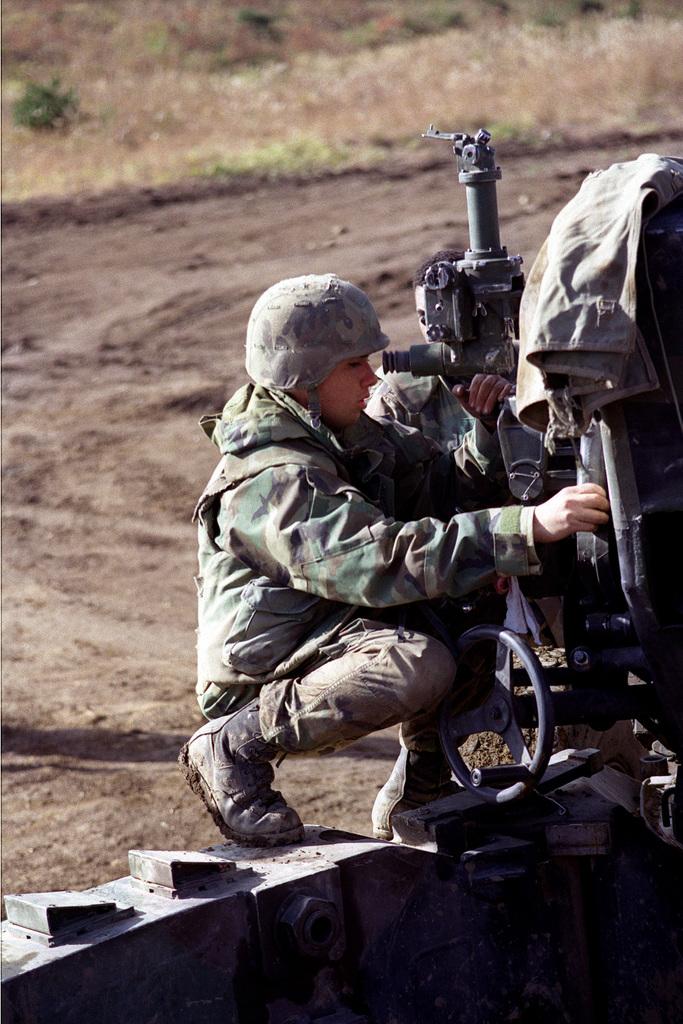 Right side profile medium shot of US Marine Lance Corporal Randy Salinas a Cannoneer from Lima Company, 3rd Battalion, 12th Marines, from Camp Hansen, Okinawa, Japan, as he looks through the sites on a M198 155mm Howitzer during one of the training exercises at the Artillery Relocation Shoot at Ojojihara, Japan
