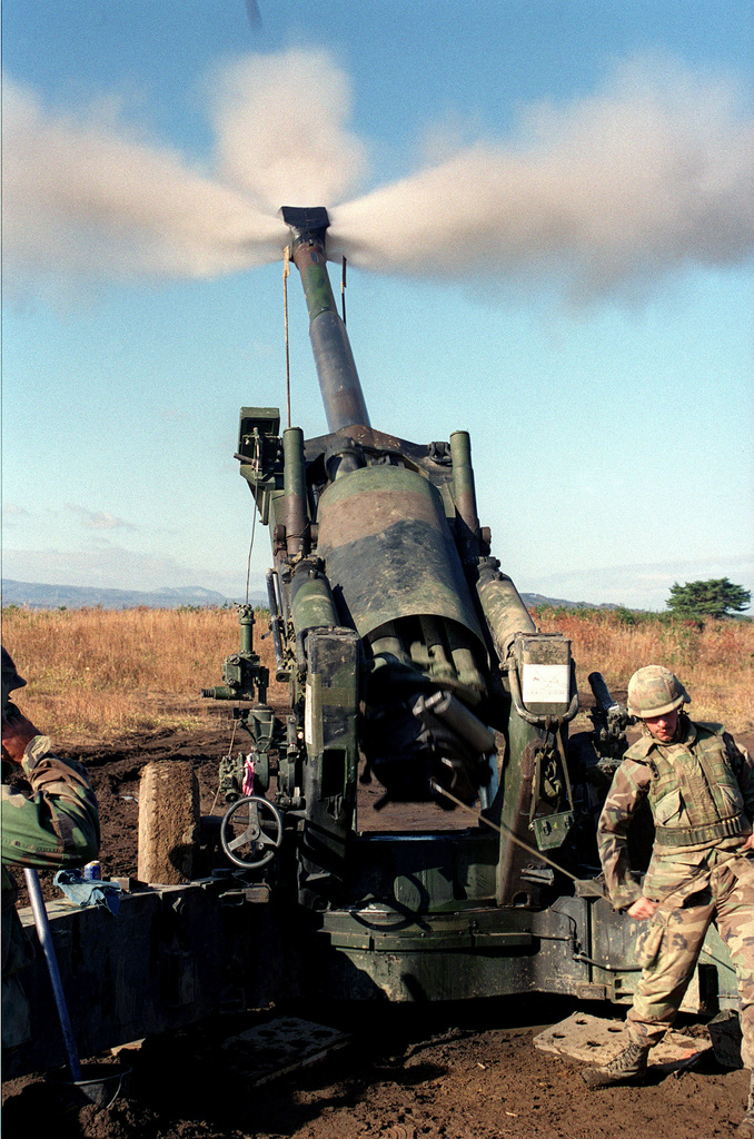 Straight on medium shot of US Marine Private First Class Ethan Fuller, a Cannoneer from Lima Company, 3rd Battalion, 12th Marines, from Camp Hansen, Okinawa, Japan, pulls the Lanyard on a M198 155mm Howitzer during one of the training exercises at the Artillery Relocation Shoot at Ojojihara, Japan