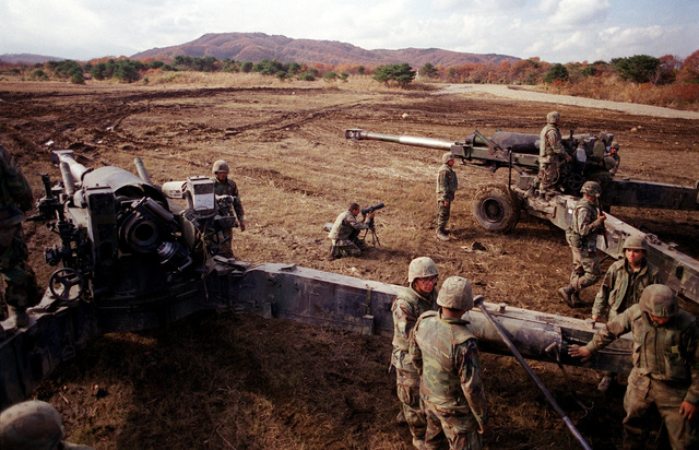 High angle rear view of two US Marine M198 155mm Howitzers as Marines from Lima Battery, 3rd Battalion, 12th Marines from Camp Hansen, Okinawa, Japan, set up the Howitzers for firing during the Artillery Relocation Shoot at Ojojihara, Japan