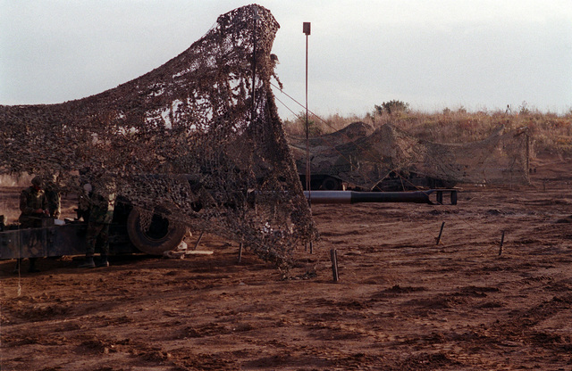 Right side profile medium shot of two US Marine M198 155mm Howitzers, covered in camouflaged netting, as Marines from Lima Battery, 3rd Battalion, 12th Marines from Camp Hansen, Okinawa, Japan, set up the Howitzers for firing during the Artillery Relocation Shoot at Ojojihara, Japan