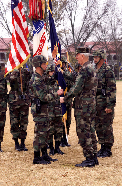 US Army General Thomas A. Schwartz (Right), outgoing Commanding General, Forces Command, watches as the flag of command is passed from him, by US Navy Admiral Harold W. Gehman Jr. (In BDU cap), Commander, Atlantic Command, to General John W. Hendrix (Left w/sidearm), incoming Commanding General, Forces Command, in ceremonies on Hedekin Field at Fort McPherson, Georgia