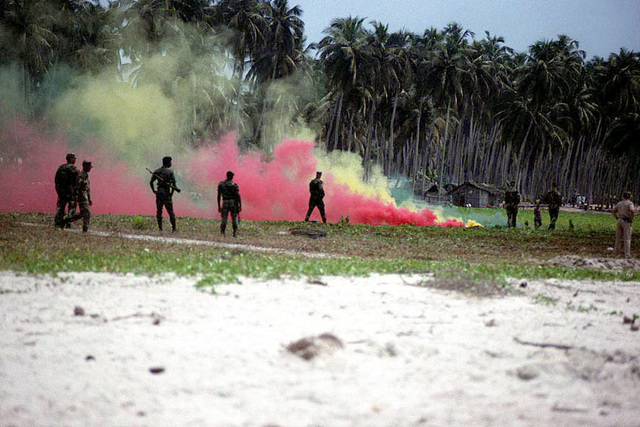US Marines from Marine Forces Unitas XL, with curious men of the Ivory Coast's military looking on, discharge their remaining multicolored smoke grenades after the completion of a training field operation at a coastal training site in Abidjan. Marines and Sailors from the USS CARTER HALL (LSD 50) were participating in this joint training operation as a part of the bi-annual West African Training Cruise (WATC)-99 deployment to western African countries which promotes interoperability and cultivates stronger ties with our foreign allies