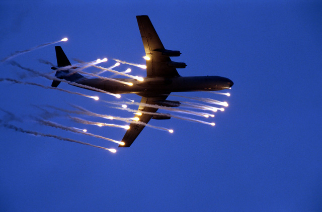 "A C-141B Starlifter from McGuire Air Force Base, New Jersey, fires off a salvo of flares on its final pass over the ""danger zone"" during a training exercise. The exercise allowed loadmasters to use a new Plexiglas bubble to look for surface-to-air missle plumes and allowed aircrew members to practice evasive maneuvers"