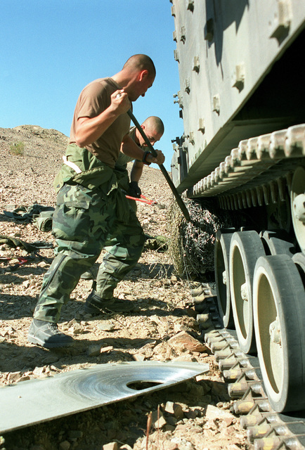 SGT Castro and CPL Sayer of Second Platoon, Bravo Company, Third Amphibious Assault Battalion, are removing a bundle of concertina wire, which was caught up in the vehicle tread, during a live fire movement exercise at Marine Corps Air Ground Combat Center, Twentynine Palms, California, during Operation Steel Knight