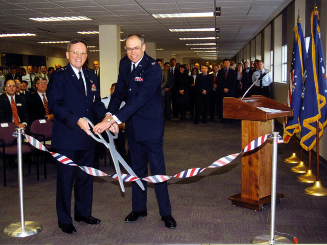 Aeronautical System Center Commander Lieutenant General Robert Raggio (Left, foreground) and ASC Director of Plans And Programs Colonel Richard Bowman cut the ribbon for the grand re-opening of Building 11A at Wright Patterson Air Force Base, Ohio, after re-hab