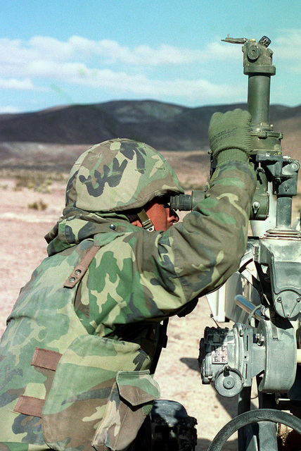 A Marine from 11th Marines Artillery, Kilo Battery, gun 3, does his part in setting up his teams howitzer (only the sighting mechanism on the howitzer is shown) during Desert Knight , a live fire exercise held at MCAGCC Twentynine Palms California in December of 1999