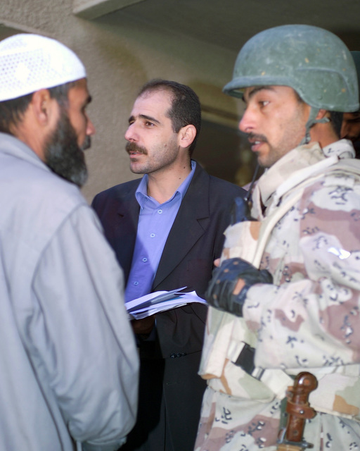 A representative of the Iraqi Ministry of Health (center) and an Iraqi Army Soldier (right) speak with an Iraqi civilian (left) in the Hadhrah Mosque, the site of an Iraqi Army controlled humanitarian assistance distribution site, in the city of Fallujah, Al Anbar Province, Iraq, on Nov. 24, 2004. Iraqi civilians are able to come to the humanitarian assistance site to receive assistance at the conclusion of the week-long battle by Multinational Forces against insurgents in the city of Fallujah, during Operation Iraqi Freedom. (U.S. Marine Corps photo by CPL. Theresa M. Medina) (Released)