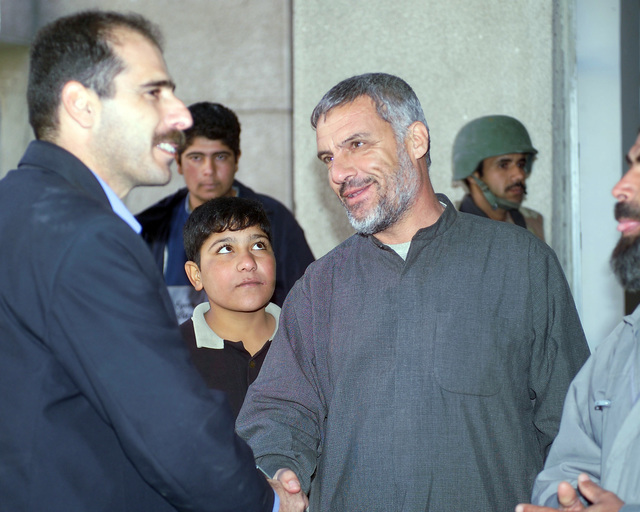 A representative of the Iraqi Ministry of Health (left) speaks with Iraqi civilians gathered at the Hadhrah Mosque, the site of an Iraqi Army controlled humanitarian assistance distribution site, in the city of Fallujah, Al Anbar Province, Iraq, on Nov. 24, 2004. Iraqi civilians are able to come to the humanitarian assistance site to receive assistance at the conclusion of the week-long battle by Multinational Forces against insurgents in the city of Fallujah, during Operation Iraqi Freedom. (U.S. Marine Corps photo by CPL. Theresa M. Medina) (Released)