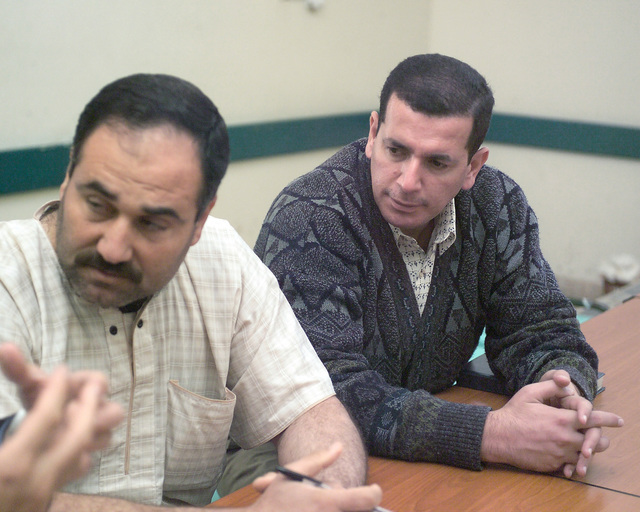 A representative of the Iraqi Ministry of Health (right) listens as an Iraqi civilian worker at the Fallujah General Hospital, in the city of Fallujah, Al Anbar Province, Iraq, speaks to a second representative of the Iraqi Ministry of Health on Nov. 24, 2004, to get a clearer assessment of the condition of the hospital and what needs to be done to improve it. U.S. Marine Corps 4th Civil Affairs Group Marines and Iraqi Ministry of Health representatives are inspecting various medical facilities to estimate what repairs are necessary to get the them back to full functionality. This assessment is being done at the conclusion of the week-long battle by Multinational Forces against...