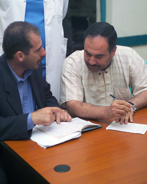 A representative of the Iraqi Ministry of Health (right) speaks with an Iraqi civilian worker at the Fallujah General Hospital, in the city of Fallujah, Al Anbar Province, Iraq, on Nov. 24, 2004, to get a clearer assessment of the condition of the hospital and what needs to be done to improve it. U.S. rine Corps 4th Civil Affairs Group rines and Iraqi Ministry of Health representatives are inspecting various medical facilities to estimate what repairs are necessary to get the them back to full functionality. This assessment is being done at the conclusion of the week-long battle by Multinational Forces against insurgents in the city of Fallujah, during Operation Iraqi Freedom. (U.S....