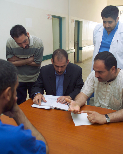 A representative of the Iraqi Ministry of Health (seated center) speaks with four Iraqi civilian workers at the Fallujah General Hospital, in the city of Fallujah, Al Anbar Province, Iraq, on Nov. 24, 2004, to get a clearer assessment of the condition of the hospital and what needs to be done to improve it. U.S. Marine Corps 4th Civil Affairs Group Marines and Iraqi Ministry of Health representatives are inspecting various medical facilities to estimate what repairs are necessary to get the them back to full functionality. This assessment is being done at the conclusion of the week-long battle by Multinational Forces against insurgents in the city of Fallujah, during Operation Iraqi...