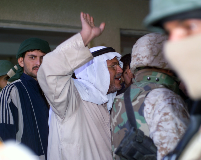 A representative of the Iraqi Ministry of Health (waving his arm) speaks with Iraqi civilians gathered at the Hadhrah Mosque, the site of an Iraqi Army controlled humanitarian assistance distribution site, in the city of Fallujah, Al Anbar Province, Iraq, on Nov. 24, 2004. Iraqi civilians are able to come to the humanitarian assistance site to receive assistance at the conclusion of the week-long battle by Multinational Forces against insurgents in the city of Fallujah, during Operation Iraqi Freedom. (U.S. Marine Corps photo by CPL. Theresa M. Medina) (Released)