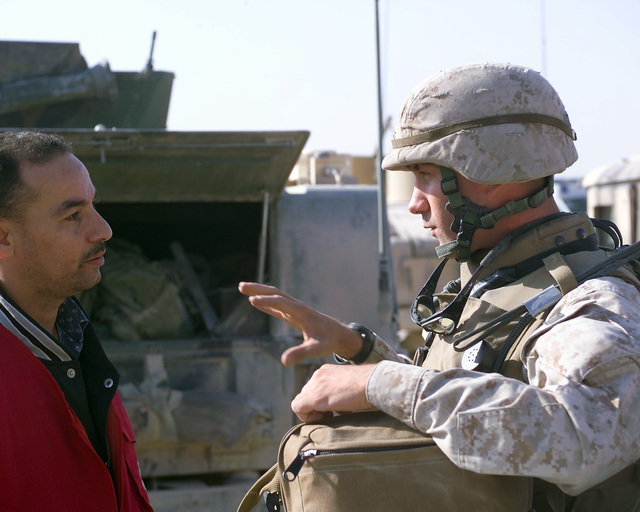 A U.S. Marine Corps 4th Civil Affairs Group, I Marine Expeditionary Force, Marine (right) speaks with an Iraqi Red Crescent worker (left) outside of the U.S. Marine Corps 4th Civil Affairs Group, Civil Military Operations Center in the city of Fallujah, Al Anbar Province, Iraq, on Nov. 22, 2004. The Red Crescent is in Fallujah to assist in transporting Iraqi civilians to medical facilities at the conclusion of the week-long battle by Multinational Forces against insurgents in the city of Fallujah, during Operation Iraqi Freedom. (U.S. Marine Corps photo by CPL. Theresa M. Medina) (Released)