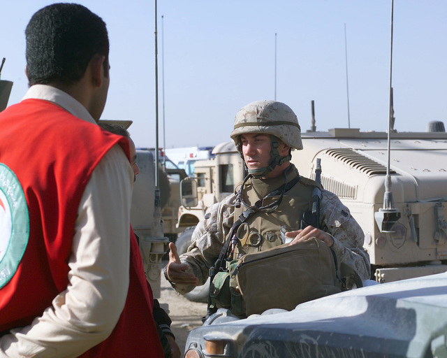 A U.S. Marine Corps 4th Civil Affairs Group, I Marine Expeditionary Force, Marine (right) speaks with an Iraqi Red Crescent worker (second from left) outside of the U.S. Marine Corps 4th Civil Affairs Group, Civil Military Operations Center in the city of Fallujah, Al Anbar Province, Iraq, on Nov. 22, 2004. The Red Crescent is in Fallujah to assist in transporting Iraqi civilians to medical facilities at the conclusion of the week-long battle by Multinational Forces against insurgents in the city of Fallujah, during Operation Iraqi Freedom. (U.S. Marine Corps photo by CPL. Theresa M. Medina) (Released)