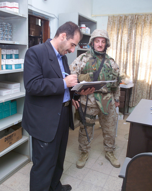 A U.S. Marine Corps 4th Civil Affairs Group Marine (right) observes as a representative of the Iraqi Ministry of Health (left) makes notes about conditions inside the Jolan Medical Clinic, in the city of Fallujah, Al Anbar Province, Iraq, that U.S. Marine Corps 4th Civil Affairs Group Marines and Iraqi Ministry of Health representatives are inspecting on Nov. 24, 2004, to estimate what repairs are necessary to get the it back to full functionality. This assessment is being done at the conclusion of the week-long battle by Multinational Forces against insurgents in the city of Fallujah, during Operation Iraqi Freedom. (U.S. Marine Corps photo by CPL. Theresa M. Medina) (Released)