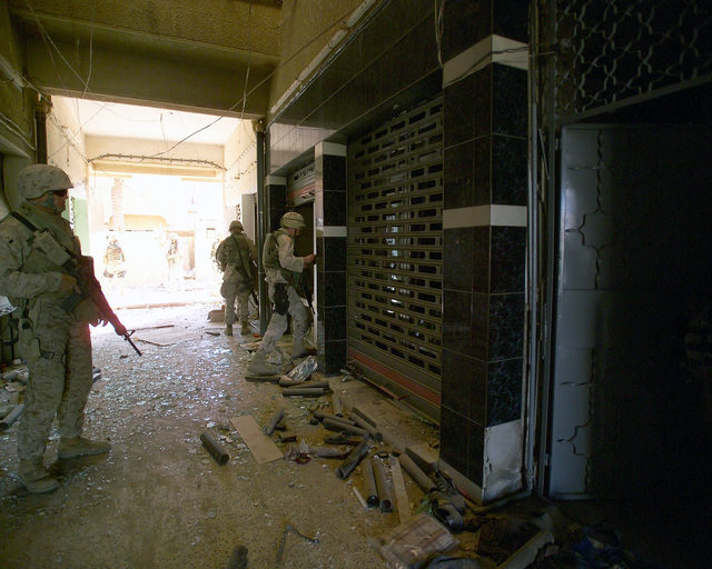 A U.S. Marine Corps Marine (left) stands security as other Marines search through rooms inside an unmarked Islamic Resistance Center building, located in the city of Fallujah, Al Anbar Province, Iraq, on Dec. 2, 2004, to clear the building prior to foreign news reporters entering the building to gather information for their news stories. The foreign media is touring various sites within the city of Fallujah to see the reconstruction efforts going on after the November battle between Multinational Forces and insurgents in the city of Fallujah, during Operation Iraqi Freedom. (U.S. Marine Corps photo by CPL. Theresa M. Medina) (Released)