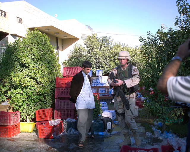 A U.S. Marine Corps Marine (right) and an Iraqi military-aged young man (left) stand in front of a shipment of bottled water that was just delivered to the front area of an Iraqi Red Crescent center, located in the city of Fallujah, Al Anbar Province, Iraq, on Dec. 2, 2004. This facility is being shown to the foreign media as part of their tour of various sites within the city of Fallujah to see the reconstruction efforts going on after the November battle between Multinational Forces and insurgents in the city of Fallujah, during Operation Iraqi Freedom. (U.S. Marine Corps photo by CPL. Theresa M. Medina) (Released)