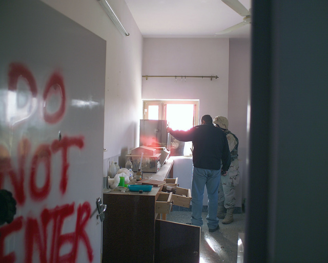 A U.S. Marine Corps Regimental Combat Team 7 (RCT-7) Marine (right) and a civilian contractor (left) stand inside a laboratory in the Dr. Talib Al-Janabi Hospital, in the city of Fallujah, Al Anbar Province, Iraq, on Nov. 23, 2004, to estimate what repairs are necessary to get the it back to full functionality. This assessment is being done at the conclusion of the week-long battle by Multinational Forces against insurgents in the city of Fallujah, during Operation Iraqi Freedom. (U.S. Marine Corps photo by CPL. Theresa M. Medina) (Released)