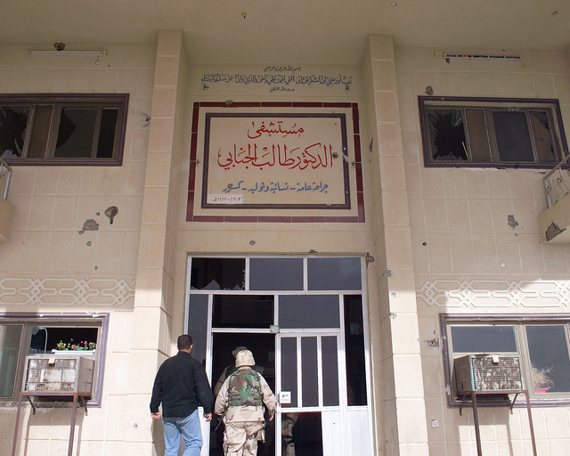A U.S. Marine Corps Regimental Combat Team 7 (RCT-7) Marine (right) and a civilian contractor (left) enter through the entrance to the Dr. Talib Al-Janabi Hospital, in the city of Fallujah, Al Anbar Province, Iraq, on Nov. 23, 2004, to estimate what repairs are necessary to get the hospital back to full functionality. This assessment is being done at the conclusion of the week-long battle by Multinational Forces against insurgents in the city of Fallujah, during Operation Iraqi Freedom. (U.S. Marine Corps photo by CPL. Theresa M. Medina) (Released)