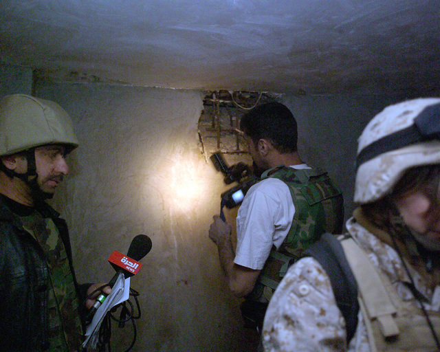 An Arab news cameraman (center, back) records a hole in the wall of a bloody basement in an unmarked Islamic Resistance Center building, located in the city of Fallujah, Al Anbar Province, Iraq, on Dec. 2, 2004. This basement may have served as a torture chamber and is being shown to the foreign media as part of their tour of various sites within the city of Fallujah to see the reconstruction efforts going on after the November battle between Multinational Forces and insurgents in the city of Fallujah, during Operation Iraqi Freedom. (U.S. Marine Corps photo by CPL. Theresa M. Medina) (Released) (SUBSTANDARD)