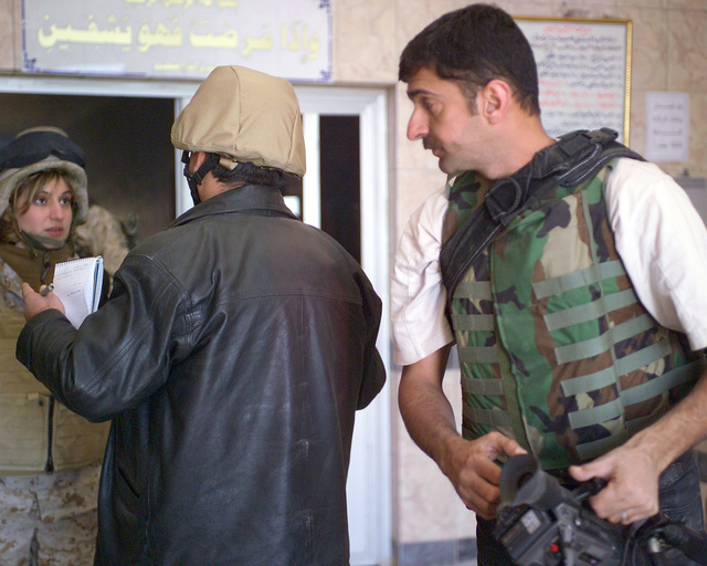 An Arab news reporter (center) speaks to 'Rose' (left), an Iraqi interpreter, as his cameraman (right) listens, inside the Dr. Talib Al-Janabi Hospital, in the city of Fallujah, Al Anbar Province, Iraq, on Dec. 2, 2004, as he prepares for his news story. The foreign media is on a tour of various sites in Fallujah to see the reconstruction efforts going on after the November battle by Multinational Forces against insurgents in the city of Fallujah, during Operation Iraqi Freedom. (U.S. Marine Corps photo by CPL. Theresa M. Medina) (Released)