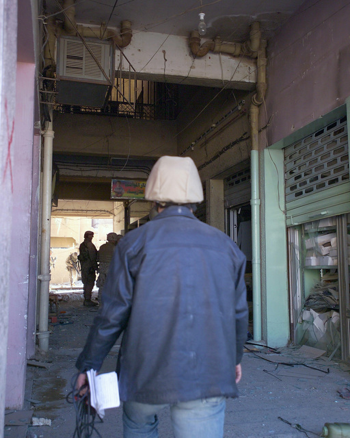 An Arab news reporter enters an unmarked Islamic Resistance Center building, just cleared by U.S. Marine Corps Marines on Dec. 2, 2004, to gather information for his news story. The foreign media is touring various sites within the city of Fallujah, Al Anbar Province, Iraq, to see the reconstruction efforts going on after the November battle between Multinational Forces and insurgents in the city of Fallujah, during Operation Iraqi Freedom. (U.S. Marine Corps photo by CPL. Theresa M. Medina) (Released)