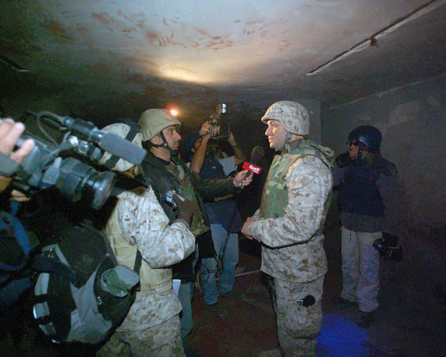 An Arab news reporter holding a microphone) interviews U.S. Marine Corps MAJ. Alex Ray second from right), Information Officer, I Marine Expeditionary Force, about the bloody finger prints and blood streaks on the walls of a bloody basement in an unmarked Islamic Resistance Center building, located in the city of Fallujah, Al Anbar Province, Iraq, on Dec. 2, 2004. This basement may have served as a torture chamber and is being shown to the foreign media as part of their tour of various sites within the city of Fallujah to see the reconstruction efforts going on after the November battle between Multinational Forces and insurgents in the city of Fallujah, during Operation Iraqi Freedom....