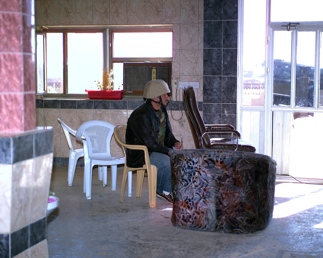 An Arab news reporter sits in a chair inside the Dr. Talib Al-Janabi Hospital, in the city of Fallujah, Al Anbar Province, Iraq, on Dec. 2, 2004, to write the notes for his news story. The foreign media is on a tour of various sites in Fallujah to see the reconstruction efforts going on after the November battle by Multinational Forces against insurgents in the city of Fallujah, during Operation Iraqi Freedom. (U.S. Marine Corps photo by CPL. Theresa M. Medina) (Released)