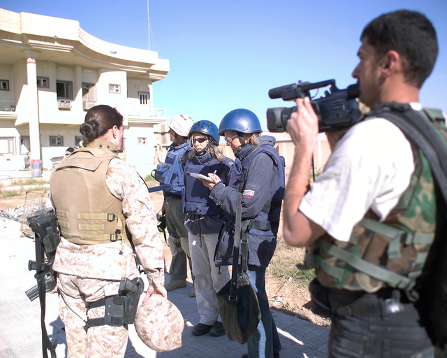 An Arab television news crew cameraman (right) records western news reporters (center) interviewing U.S. Marine Corps MAJ. M. Naomi Hawkins (left, back to camera), Public Affairs Officer, 4th Civil Affairs Group, in front of the Dr. Talib Al-Janabi Hospital, in the city of Fallujah, Al Anbar Province, Iraq, on Dec. 2, 2004. The foreign media is on a tour of various sites in Fallujah to see the reconstruction efforts going on after the November battle by Multinational Forces against insurgents in the city of Fallujah, during Operation Iraqi Freedom. (U.S. Marine Corps photo by CPL. Theresa M. Medina) (Released)