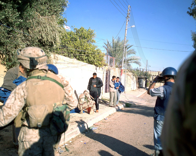 An Iraqi Army Soldier (center, kneeling) searches the bags of the Iraqi man standing in front of him before allowing him to enter an Iraqi Red Crescent center, located in the city of Fallujah, Al Anbar Province, Iraq, on Dec. 2, 2004. This facility is being shown to the foreign media as part of their tour of various sites within the city of Fallujah to see the reconstruction efforts going on after the November battle between Multinational Forces and insurgents in the city of Fallujah, during Operation Iraqi Freedom. (U.S. Marine Corps photo by CPL. Theresa M. Medina) (Released)