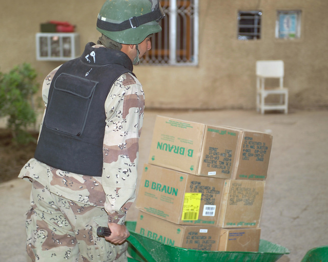An Iraqi Army Soldier (front) moves medical supplies into the Hadhrah Mosque, the site of an Iraqi Army controlled humanitarian assistance distribution site, in the city of Fallujah, Al Anbar Province, Iraq, on Nov. 23, 2004. Iraqi civilians are able to come to the humanitarian assistance site to receive assistance at the conclusion of the week-long battle by Multinational Forces against insurgents in the city of Fallujah, during Operation Iraqi Freedom. (U.S. Marine Corps photo by CPL. Theresa M. Medina) (Released)