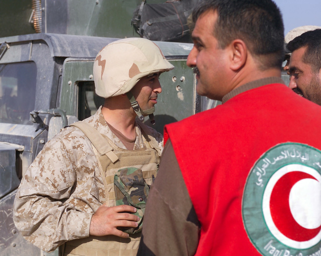 An Iraqi Army Soldier (left) speaks with an Iraqi Red Crescent worker (right) outside of the U.S. Marine Corps 4th Civil Affairs Group, Civil Military Operations Center in the city of Fallujah, Al Anbar Province, Iraq, on Nov. 22, 2004. The Red Crescent is in Fallujah to assist in transporting Iraqi civilians to medical facilities at the conclusion of the week-long battle by Multinational Forces against insurgents in the city of Fallujah, during Operation Iraqi Freedom. (U.S. Marine Corps photo by CPL. Theresa M. Medina) (Released)