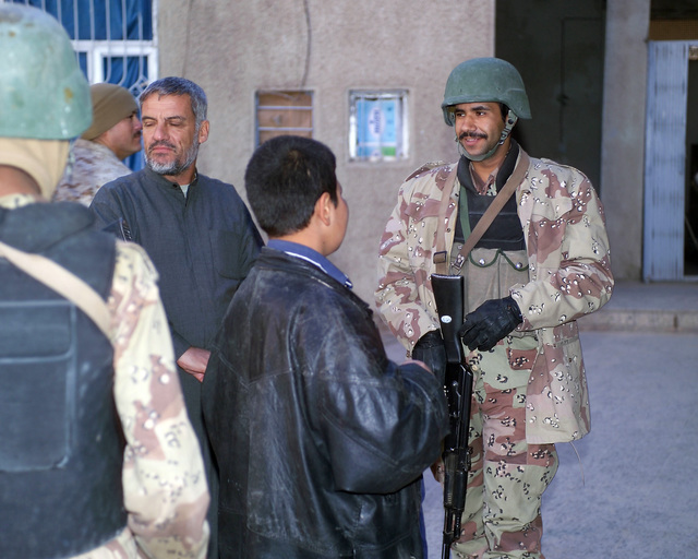 An Iraqi Army Soldier (right) speaks with an Iraqi young man (center) in the Hadhrah Mosque, the site of an Iraqi Army controlled humanitarian assistance distribution site, in the city of Fallujah, Al Anbar Province, Iraq, on Nov. 24, 2004. Iraqi civilians are able to come to the humanitarian assistance site to receive assistance at the conclusion of the week-long battle by Multinational Forces against insurgents in the city of Fallujah, during Operation Iraqi Freedom. (U.S. Marine Corps photo by CPL. Theresa M. Medina) (Released)