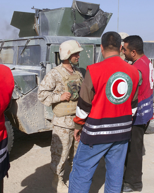 An Iraqi Army Soldier (second from left) speaks with an Iraqi Red Crescent worker (right) outside of the U.S. Marine Corps 4th Civil Affairs Group, Civil Military Operations Center in the city of Fallujah, Al Anbar Province, Iraq, on Nov. 22, 2004. The Red Crescent is in Fallujah to assist in transporting Iraqi civilians to medical facilities at the conclusion of the week-long battle by Multinational Forces against insurgents in the city of Fallujah, during Operation Iraqi Freedom. (U.S. Marine Corps photo by CPL. Theresa M. Medina) (Released)