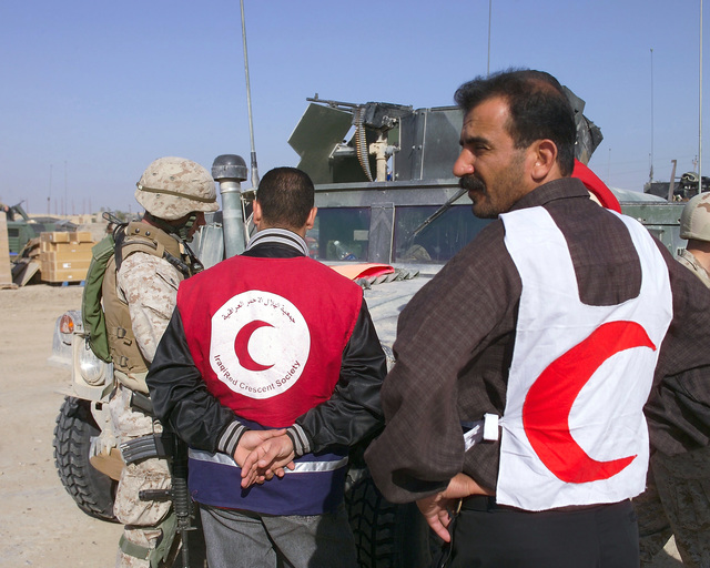 An Iraqi Red Crescent worker (center) speaks with a U.S. Marine Corps 4th Civil Affairs Group, I Marine Expeditionary Force, Marine (left) outside of the U.S. Marine Corps 4th Civil Affairs Group, Civil Military Operations Center in the city of Fallujah, Al Anbar Province, Iraq, on Nov. 22, 2004. The Red Crescent is in Fallujah to assist in transporting Iraqi civilians to medical facilities at the conclusion of the week-long battle by Multinational Forces against insurgents in the city of Fallujah, during Operation Iraqi Freedom. (U.S. Marine Corps photo by CPL. Theresa M. Medina) (Released)