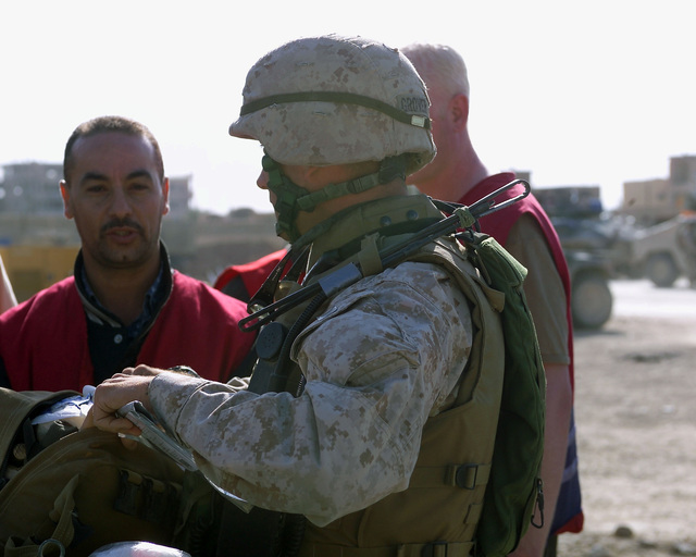 An Iraqi Red Crescent worker (left) speaks with a U.S. Marine Corps 4th Civil Affairs Group, I Marine Expeditionary Force, Marine (front) outside of the U.S. Marine Corps 4th Civil Affairs Group, Civil Military Operations Center in the city of Fallujah, Al Anbar Province, Iraq, on Nov. 22, 2004. The Red Crescent is in Fallujah to assist in transporting Iraqi civilians to medical facilities at the conclusion of the week-long battle by Multinational Forces against insurgents in the city of Fallujah, during Operation Iraqi Freedom. (U.S. Marine Corps photo by CPL. Theresa M. Medina) (Released)