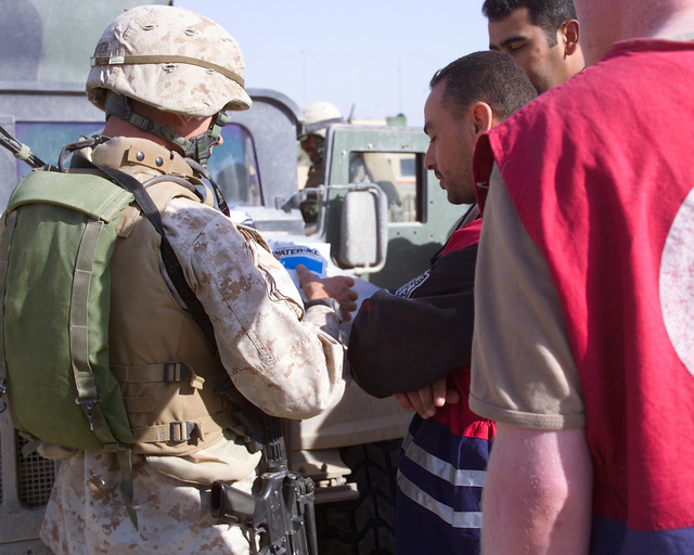 An Iraqi Red Crescent worker (second from left) speaks with a U.S. Marine Corps 4th Civil Affairs Group, I Marine Expeditionary Force, Marine (left) outside of the U.S. Marine Corps 4th Civil Affairs Group, Civil Military Operations Center in the city of Fallujah, Al Anbar Province, Iraq, on Nov. 22, 2004. The Red Crescent is in Fallujah to assist in transporting Iraqi civilians to medical facilities at the conclusion of the week-long battle by Multinational Forces against insurgents in the city of Fallujah, during Operation Iraqi Freedom. (U.S. Marine Corps photo by CPL. Theresa M. Medina) (Released)