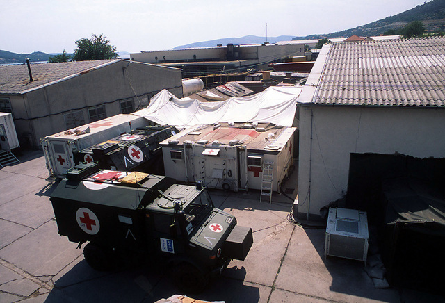 An overhead view of a Franco-German MASH site located at the Naval Base in Troger, Croatia. In the foreground is a parked Mercedes-Benz Unimog U 1350 L (4x4) Ambulance and a Transportpanzer 1 (Fuchs) Armored Personnel Carrier (APC) Ambulance parked between two temporary shelters
