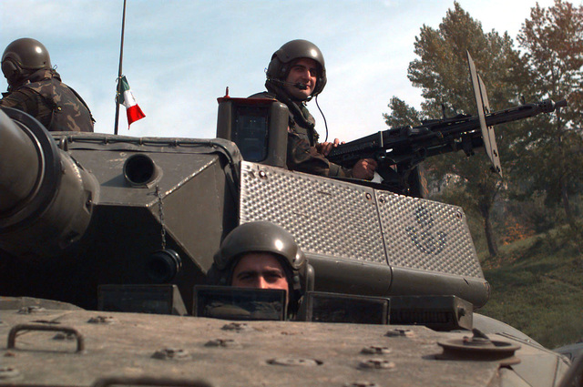 Close-up shot of three crewmembers each standing up through the two turret hatches and the driver's hatch of an Italian Army 19th Cavalry Regiment Consortium IVECO - OTO Melara Centauro B1 (8x8) Tank Destroyer. The Italian Army is in Bosnia during Operation Joint Endeavor, which is a peacekeeping effort by a multinational Implementation Force (IFOR), comprised of NATO and non-NATO military forces, deployed to Bosnia in support of the Dayton Peace Accords