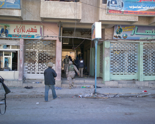Foreign news reporters enter an unmarked Islamic Resistance Center building, just cleared by U.S. Marine Corps Marines on Dec. 2, 2004, to gather information for their news stories. The foreign media is touring various sites within the city of Fallujah, Al Anbar Province, Iraq, to see the reconstruction efforts going on after the November battle between Multinational Forces and insurgents in the city of Fallujah, during Operation Iraqi Freedom. (U.S. Marine Corps photo by CPL. Theresa M. Medina) (Released)
