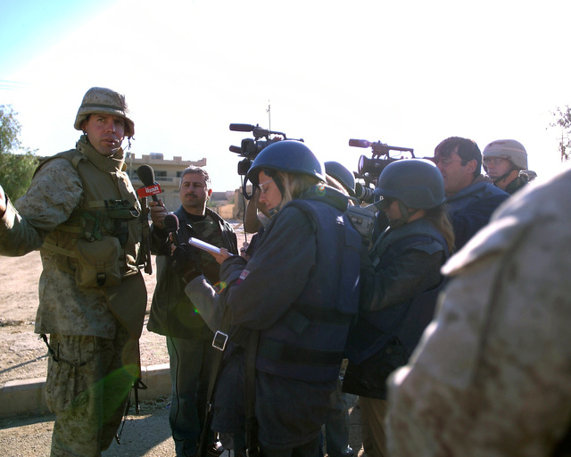 Foreign reporters interview a U.S. Marine Corps CAPT. (left) in front of an Iraqi Red Crescent center, located in the city of Fallujah, Al Anbar Province, Iraq, on Dec. 2, 2004. This facility is being shown to the foreign media as part of their tour of various sites within the city of Fallujah to see the reconstruction efforts going on after the November battle between Multinational Forces and insurgents in the city of Fallujah, during Operation Iraqi Freedom. (U.S. Marine Corps photo by CPL. Theresa M. Medina) (Released)