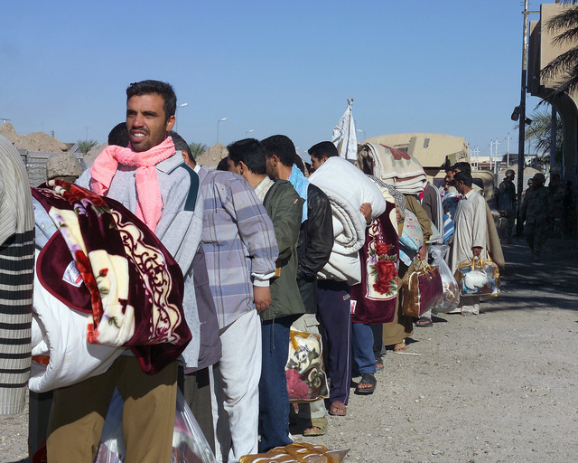 Iraqi civilians stand in a line outside the Hadhrah Mosque, the site of an Iraqi Army controlled humanitarian assistance distribution site, in the city of Fallujah, Al Anbar Province, Iraq, after receiving blankets and food on Nov. 24, 2004. Iraqi civilians are able to come to the humanitarian assistance site to receive assistance at the conclusion of the week-long battle by Multinational Forces against insurgents in the city of Fallujah, during Operation Iraqi Freedom. (U.S. Marine Corps photo by CPL. Theresa M. Medina) (Released)