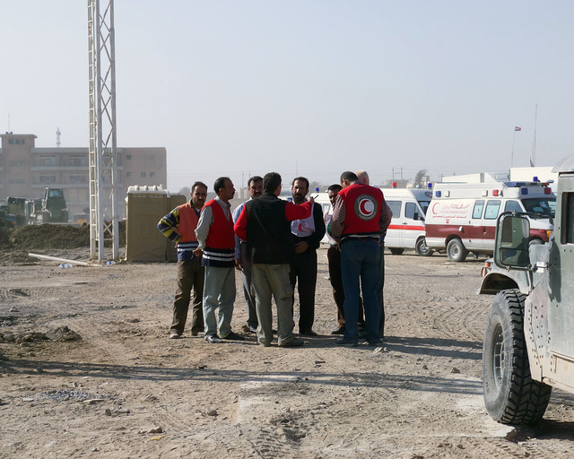 Iraqi Red Crescent workers are staged outside of the U.S. Marine Corps 4th Civil Affairs Group, Civil Military Operations Center in the city of Fallujah, Al Anbar Province, Iraq, on Nov. 22, 2004. They are in Fallujah to assist in transporting Iraqi civilians to medical facilities at the conclusion of the week-long battle by Multinational Forces against insurgents in the city of Fallujah, during Operation Iraqi Freedom. (U.S. Marine Corps photo by CPL. Theresa M. Medina) (Released)