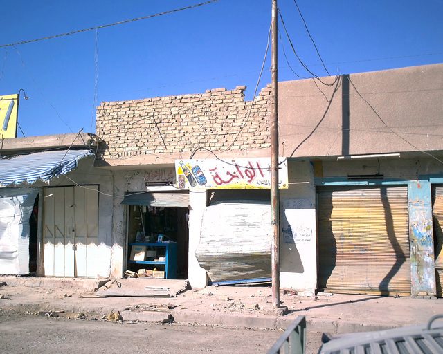 This store is located in the city of Fallujah, Al Anbar Province, Iraq, and is directly across the street from an unmarked Islamic Resistance Center building that U.S. Marine Corps Marines are clearing on Dec. 2, 2004, prior to foreign news reporters entering it as part of their tour through Fallujah. The foreign media is on a tour of various sites in Fallujah to see the reconstruction efforts going on after the November battle by Multinational Forces against insurgents in the city of Fallujah, during Operation Iraqi Freedom. (U.S. Marine Corps photo by CPL. Theresa M. Medina) (Released)