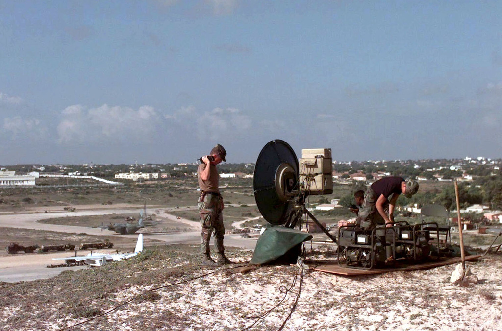 TSGT Jack Richards, USAF, a Wide Band SPECIALIST, standing at left of frame; SGT Derrick Hawkins, Switch 39A Technician, kneeling behind the communications dish; and A1C Charles Layne, a Wide Band SPECIALIST, bent over the equipment. All are conducting their daily maintenance inspection on a Tropo Satellite Support Radio Microwave Dish during Operation Restore Hope. The AIRMAN are all assigned to 5th Combat Communications Squadron, Robbins Air Force, Georgia and are providing telephone communications support to the forces assigned around Mogadishu Airport in support of Operation Restore Hope