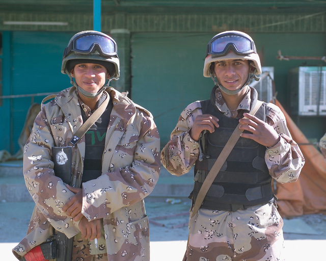 Two Iraqi Army Soldiers pose for a photograph while standing outside the Hadhrah Mosque, the site of an Iraqi Army controlled humanitarian assistance distribution site, in the city of Fallujah, Al Anbar Province, Iraq, on Nov. 24, 2004. Iraqi civilians are able to come to the humanitarian assistance site to receive assistance at the conclusion of the week-long battle by Multinational Forces against insurgents in the city of Fallujah, during Operation Iraqi Freedom. (U.S. Marine Corps photo by CPL. Theresa M. Medina) (Released)