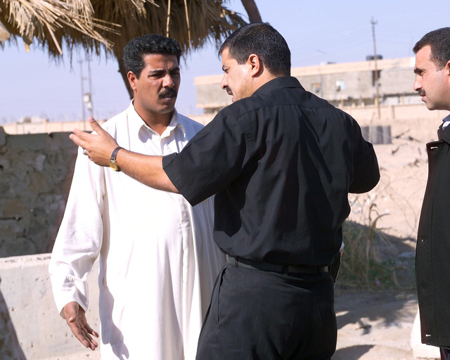 Two Jordanian Medical Doctors (center and right) talk with an Iraqi father (left) about his two sons at an Iraqi Army controlled humanitarian assistance site on Nov. 20, 2004, in the city of Fallujah, Al Anbar Province, Iraq. His younger son is sick and will be taken to a Jordanian operated hospital by an armed military convoy. Iraqi civilians are able to come to this site to receive humanitarian assistance at the conclusion of the week-long battle by Multinational Forces against insurgents in the city of Fallujah, during Operation Iraqi Freedom. (U.S. Marine Corps photo by CPL. Theresa M. Medina) (Released)