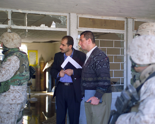 Two representatives of the Iraqi Ministry of Health (center) assess the damaged condition of the Al Wehda Medical Clinic, in the city of Fallujah, Al Anbar Province, Iraq, on Nov. 24, 2004. U.S. Marine Corps 4th Civil Affairs Group Marines and Iraqi Ministry of Health representatives are inspecting various medical facilities to estimate what repairs are necessary to get them back to full functionality. This assessment is being done at the conclusion of the week-long battle by Multinational Forces against insurgents in the city of Fallujah, during Operation Iraqi Freedom. (U.S. Marine Corps photo by CPL. Theresa M. Medina) (Released)